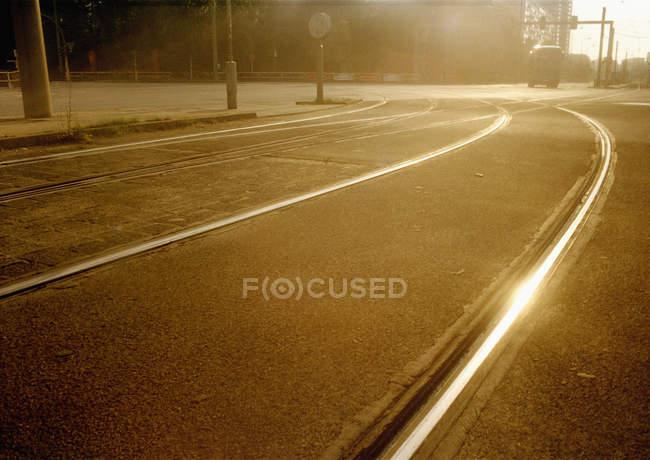 Rails du tramway sur la route goudronnée qui reflète la lumière du soleil à la scène de rue — Photo de stock