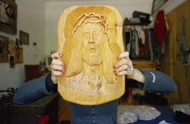 Frau mit Schnitzen von Jesus vor Gesicht — Stockfoto