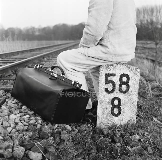 Pessoa da colheita com saco de bagagem vintage sentado no post ao lado de trilhos de trem — Fotografia de Stock