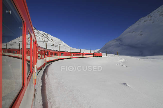 View from window of train traveling through snow-covered mountain valley — Stock Photo