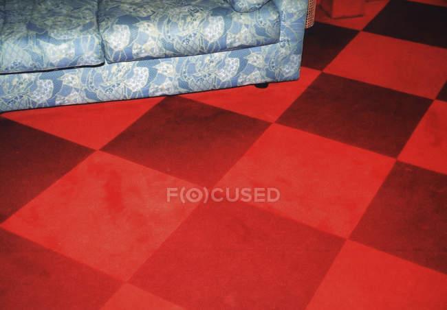 Голубая карета с цветочным узором на красном клетчатом полу — стоковое фото
