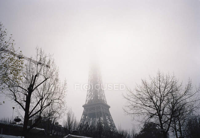 Low angle view of Eiffel tower in haze — Stock Photo