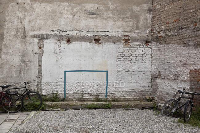 Patio con porteros dibujados en la pared y bicicletas aparcadas - foto de stock