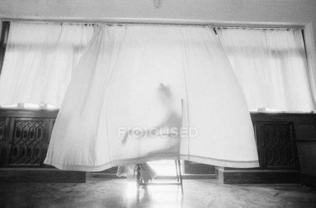 Silhouette of woman covered by curtain sitting in chair — Stock Photo
