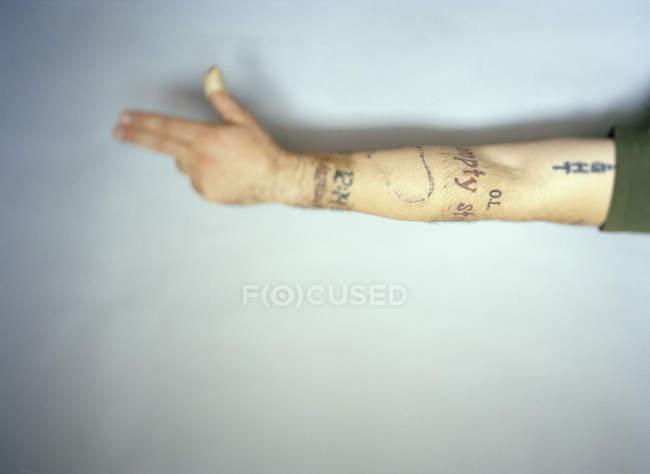 Культур вытянутыми татуированные мужской руки на белом фоне — стоковое фото