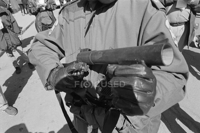 Crop riot policeman holding tear gas launcher — Stock Photo