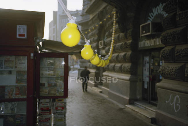 String of yellow bulb lights hanging at street scene — Stock Photo