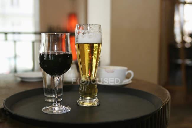 Nahaufnahme der Gläser Wein und Bier auf Tablett am Café-Tisch — Stockfoto