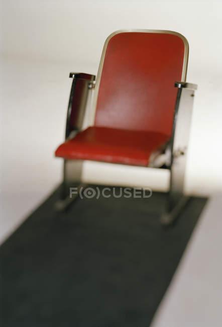 Close-up vista da poltrona miniatura vermelho sobre fundo branco — Fotografia de Stock