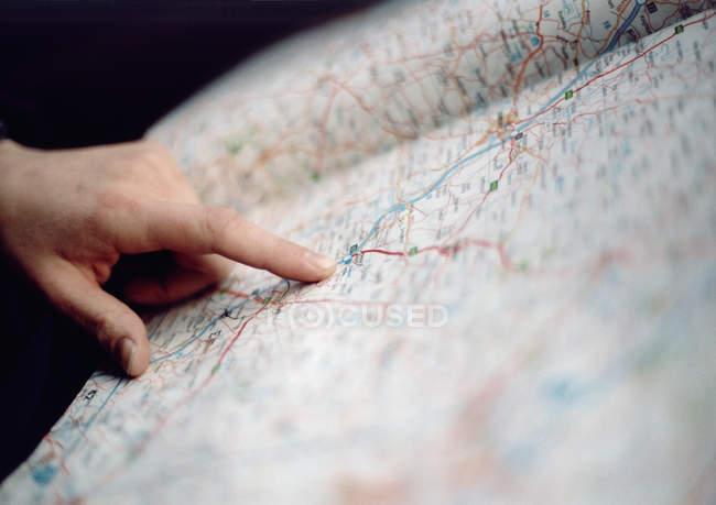 Урожай руку, указывая пальцем на дорожной карте — стоковое фото