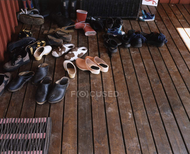 High angle view of pile of shoes on wooden boards floor — Stock Photo