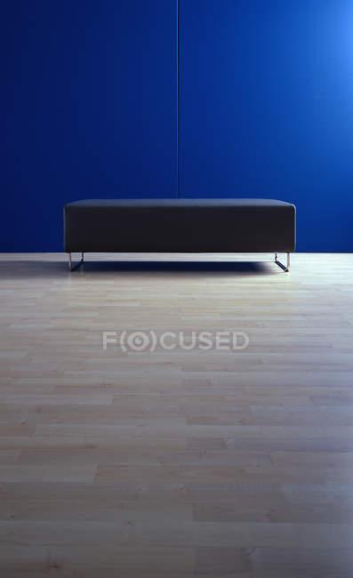 Black sofa at minimalism interior with blue wall — Stock Photo