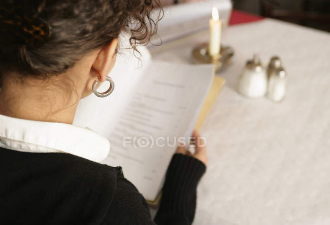 Over shoulder view of brunette woman reading menu at table in cafe — Stock Photo