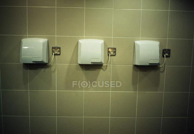 Linha de secadores de mão na parede no banheiro — Fotografia de Stock