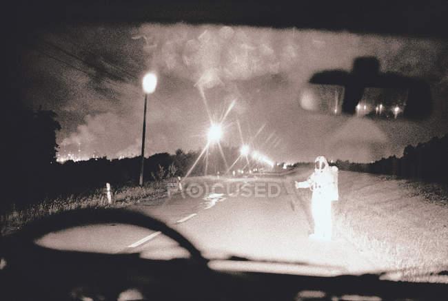Vista a través de vidrio de viento de la persona en traje de astronauta autostop en la carretera - foto de stock