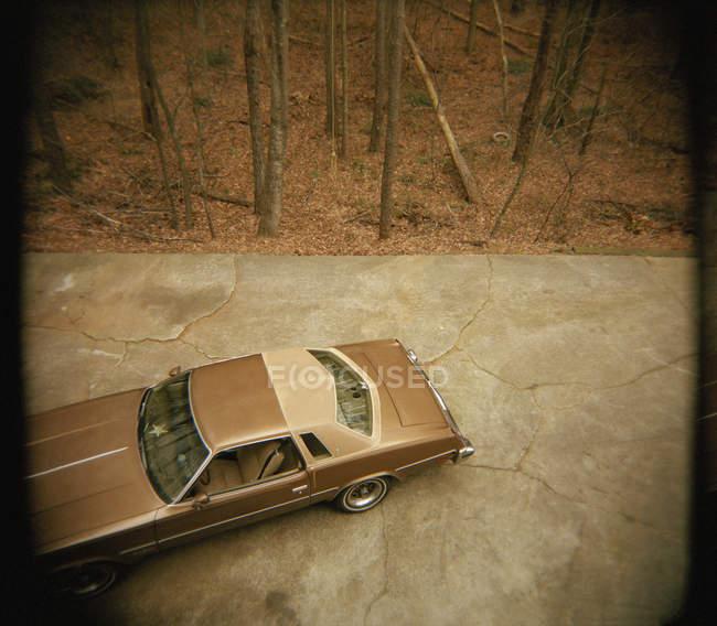 Vista de ángulo alto para coches de época aparcado en el pavimento de piedra al lado de bosque de otoño - foto de stock