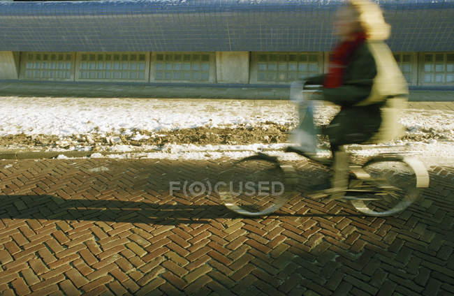 Side view of blurred woman riding bicycle at winter street — Stock Photo