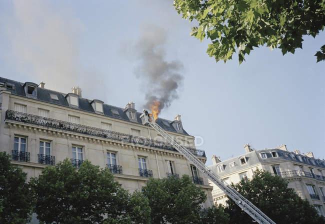 Вогонь винищувачів сходи спираючись вікна з вогнем полум'я на даху — стокове фото