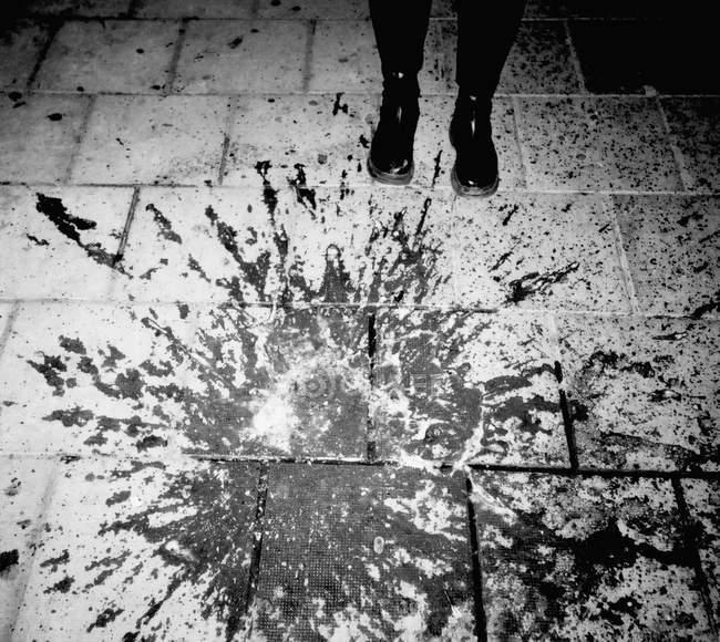 Visão de baixo ângulo de tinta preta salpicada na calçada — Fotografia de Stock