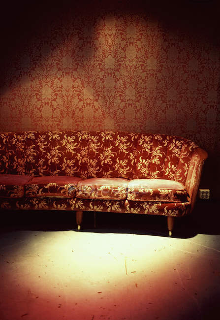 Sun beams spot on red sofa in room with red wallpaper — Stock Photo