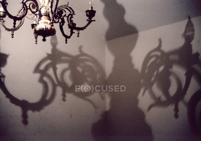 Crop chandelier and grotesque shadow on wall — Stockfoto