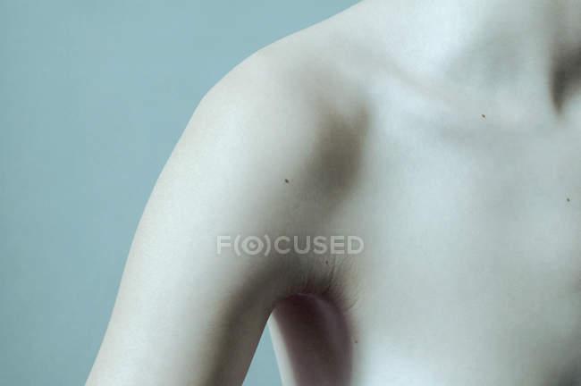 Cosecha mujer desnuda hombro sobre fondo azul - foto de stock