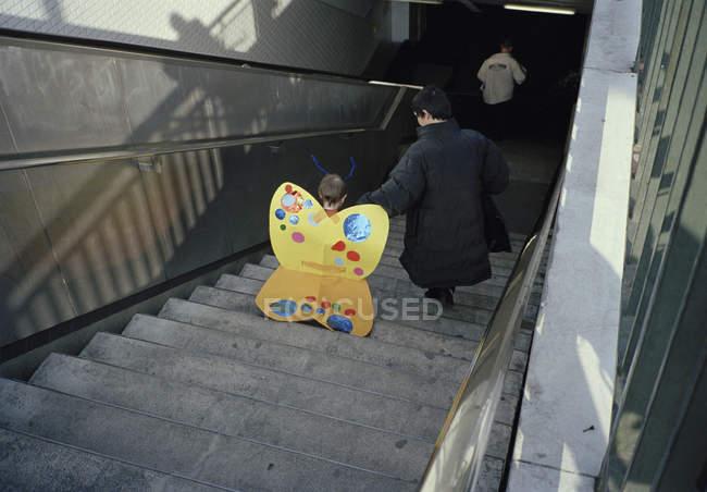 Visão traseira da criança em traje de borboleta descendo escadas — Fotografia de Stock