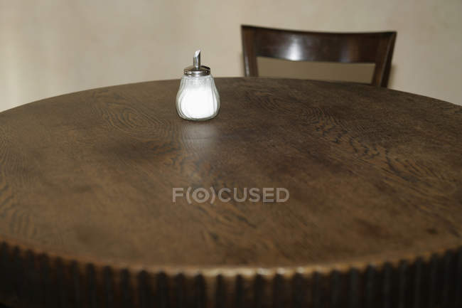 Close up view of sugar shaker on empty cafe table — Stock Photo