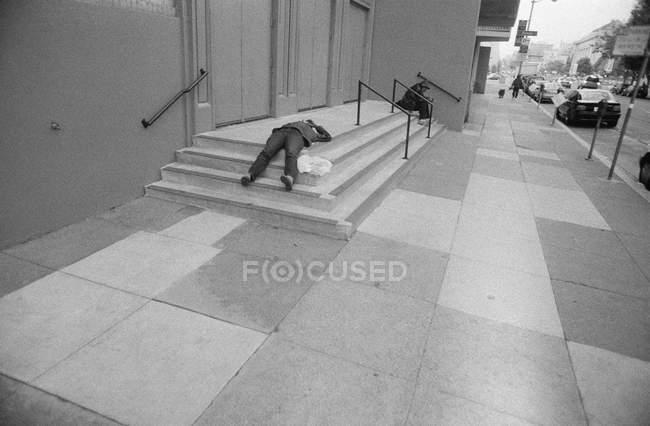Street scene with men lying on concrete staircase — Stock Photo
