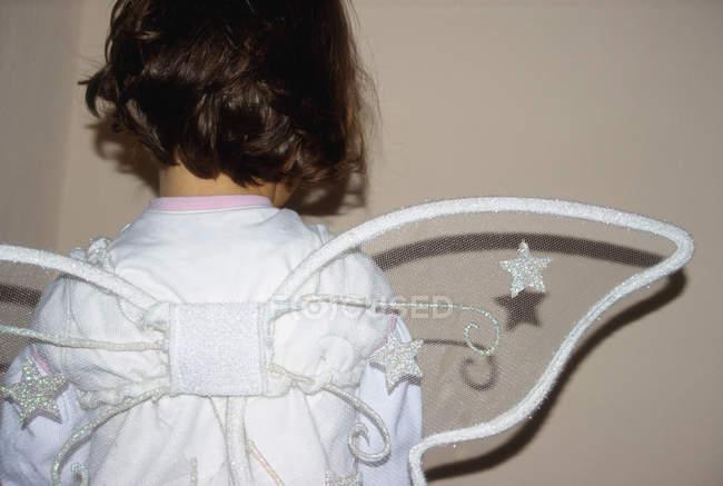 Visão traseira da criança vestindo traje de anjo com asas — Fotografia de Stock
