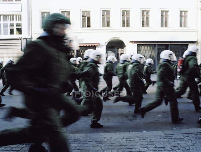 Вид сбоку на отряд ОМОНа, бегущий по улице — стоковое фото