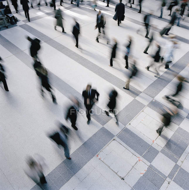 Low angle view of businesspeople walking through concourse — Stock Photo