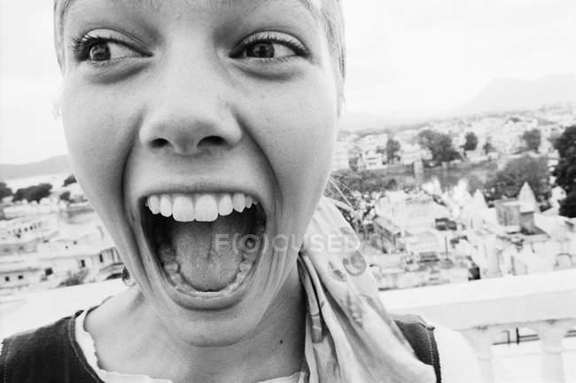 Uma mulher sorrindo enquanto olha para ela bem acima de uma cidade — Fotografia de Stock