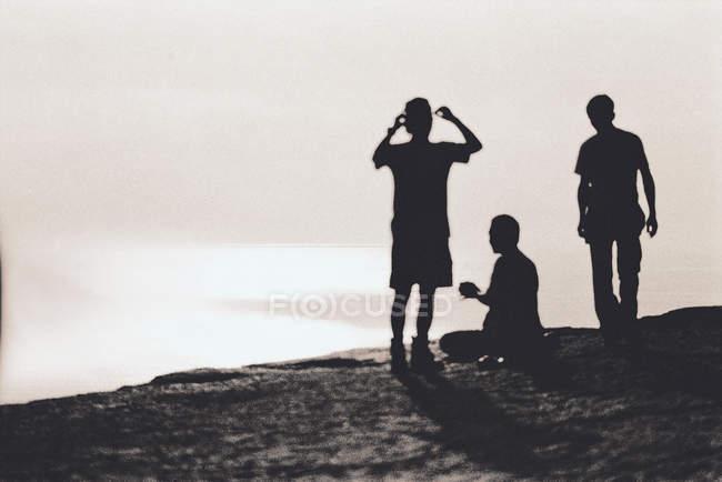 Силуэты трех человек, стоящих на скале над океаном — стоковое фото
