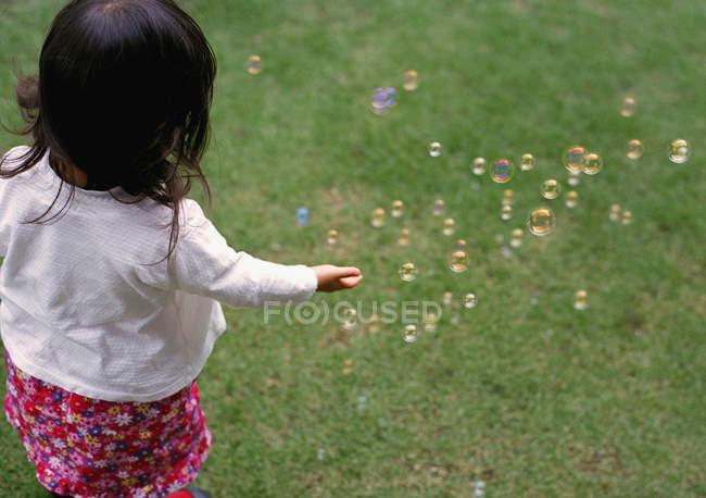 Rückansicht eines Mädchens, das Blasen auf dem grünen Rasen fängt — Stockfoto