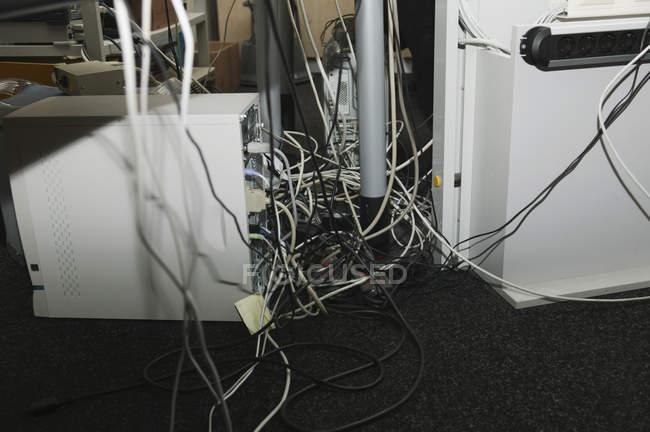 Vista de cerca de los cables de computadora debajo de la mesa - foto de stock