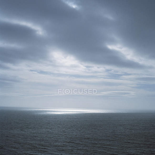 Dark clouds over ocean waves with light spot — Stock Photo