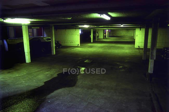 Interno vuoto verde illuminato garage sotterraneo — Foto stock