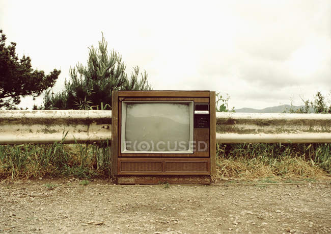 Vintage television on dirt path at countryside — Stock Photo