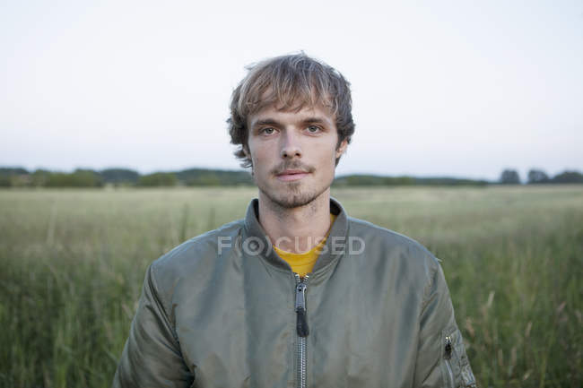 Profile of young man in jacket standing in field — Stock Photo