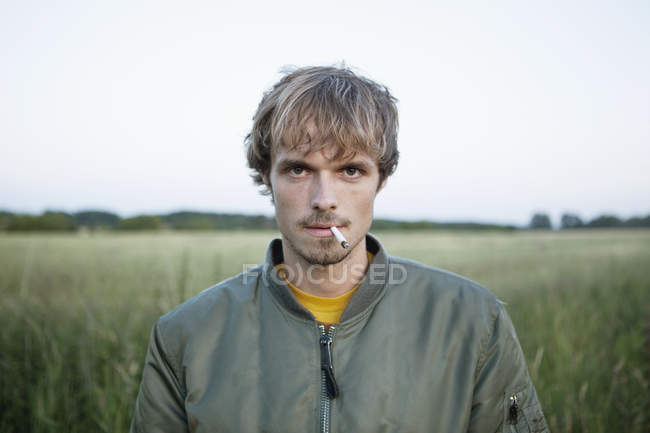 Profile of man standing in secluded field with cigarette in mouth — Stock Photo