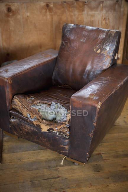 Close-up vista da velha poltrona de couro resistido com almofada rasgada — Fotografia de Stock