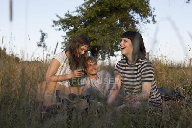 Three friends enjoying sitting in secluded field with wine and guitar — Stock Photo