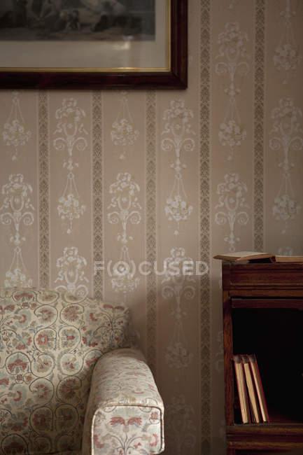Урожай богато украшенный интерьер гостиной с креслом и книжная полка — стоковое фото