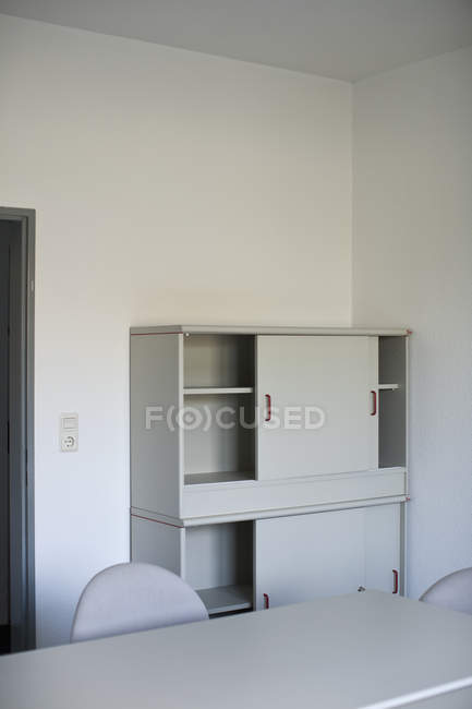 Interior of new room with empty table and wardrobe — Stock Photo