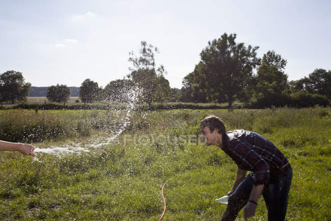 Human hand spraying man with hose on field — Stock Photo