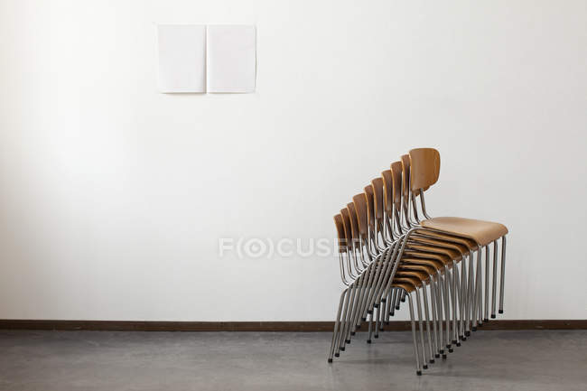 Side view of stack of chairs on background of white wall — Stock Photo