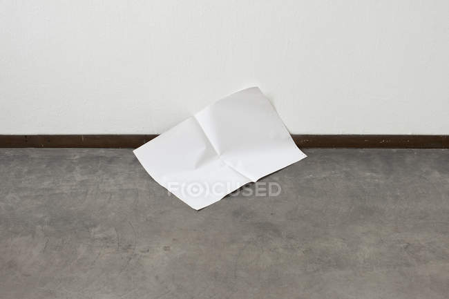 Lone sheet of paper on floor — Stock Photo