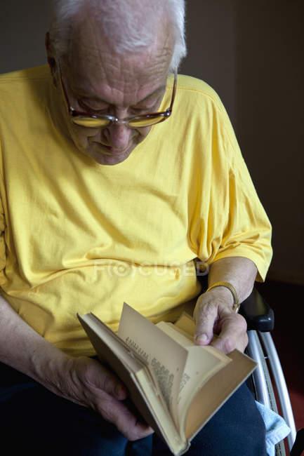 Старший человек в инвалидном кресле, листающий книгу — стоковое фото