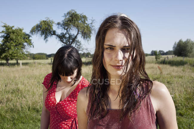 Portrait of young woman standing in field with female friend on background — Stock Photo